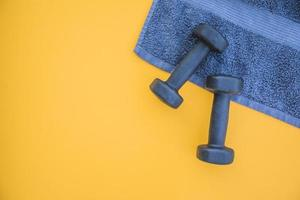Blue dumbbells and towel on yellow background photo
