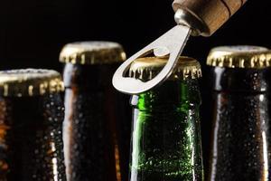 Cerrar abriendo una cerveza sobre fondo negro foto