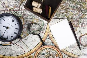 Vista elevada del reloj y la lupa en el colorido mapa antiguo foto