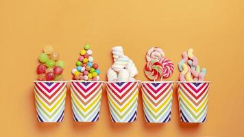 Flat lay delicious colorful candies on orange background photo