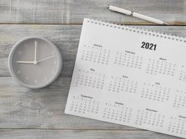 Flat lay desk calendar and analog clock photo