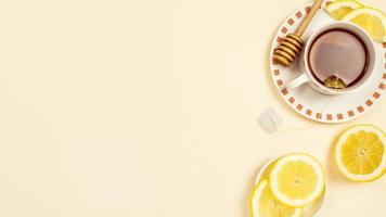 Té negro con rodajas de limón fresco sobre fondo beige foto