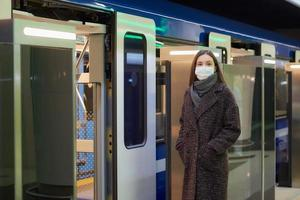 A girl in a surgical face mask is keeping social distance on a subway station photo