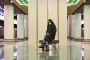 A woman in a medical face mask is waiting for a train and holding a smartphone photo