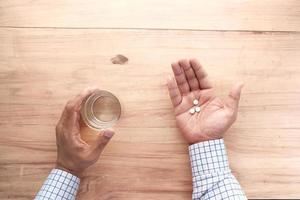 Top view of a person holding pills and water photo