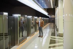 un hombre con una máscara facial está usando un teléfono inteligente mientras espera un tren subterráneo foto