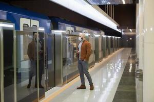 un hombre con una máscara facial sostiene un teléfono inteligente mientras espera un tren subterráneo foto