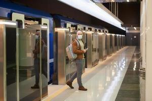 El hombre con una mascarilla médica sostiene un teléfono mientras deja un vagón de metro moderno foto