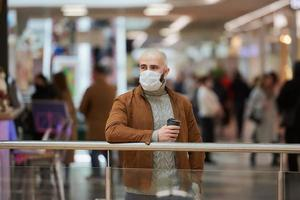 A man in a face mask is holding a cup of coffee in the shopping center photo