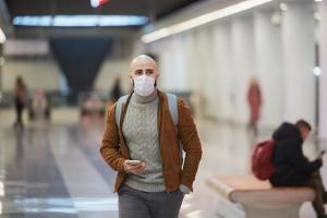 A man in a face mask is using a smartphone while waiting for a subway train photo