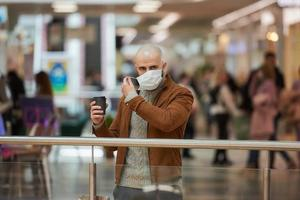 A man is putting on a mask while holding a cup of coffee in the shopping center photo