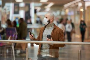 Man in a face mask is using a phone and holding a coffee in the shopping center photo