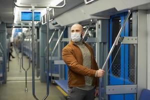 Un hombre calvo con barba en una mascarilla está sosteniendo el pasamanos en un vagón de metro foto
