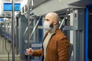 A bald man with a beard in a face mask is holding the handrail in a subway car photo