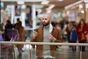 A man is holding a took-off mask while drinking coffee in the shopping center photo