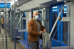 Un hombre calvo con barba en una máscara facial se está poniendo una mochila en un vagón de metro foto