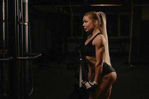 A fit woman with long blonde hair is doing a triceps rope pushdown in a gym photo