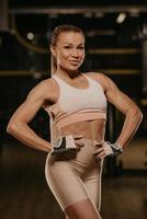 A fit woman with blonde hair is posing with her hands at her waist in a gym photo