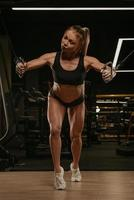 A woman with blonde hair is doing a chest workout on the cable machine in a gym photo