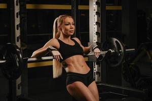A fit woman with blonde hair is laying on a barbell at the squat rack in a gym photo