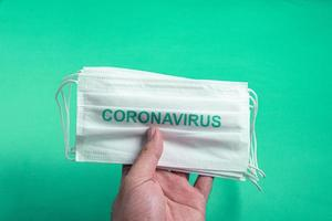 Man's hand holding a corona virus surgical mask photo