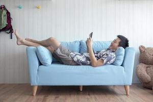 Happy young man lying on couch playing tablet at home in living room photo