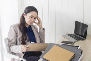 Asian business woman with headache at office photo