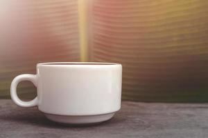 Taza de café con leche sobre fondo de hoja de plátano foto