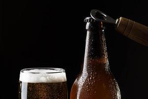 Cerca de cerveza sobre fondo negro foto