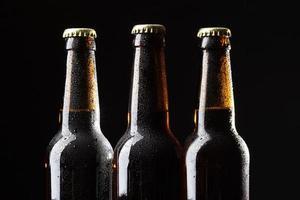 Tres botellas de cerveza sobre fondo negro foto