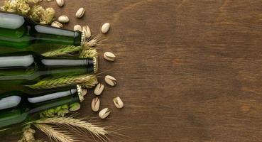 cerveza, trigo y pistachos sobre madera foto