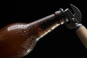 Abriendo una botella de cerveza sobre fondo negro foto