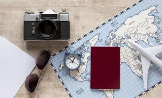 vista superior de artículos de viaje, mapa, pasaporte y cámara foto