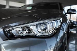 primer plano de coche de lujo moderno. concepto de auto deportivo caro. Lámpara de faro de coches nuevos, copie el espacio. un coche moderno y elegante iluminado foto