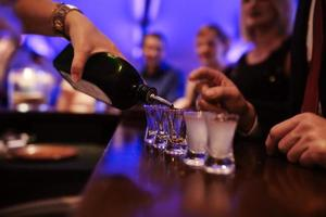Bartender pouring strong alcoholic drink into small glasses on bar, shots in a nightclub or bar photo