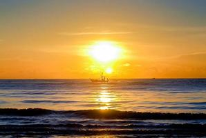 Sunset over the sea in the evening, boat sailing on the sea photo