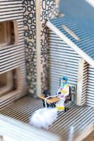 Miniature people, woman sewing on a sewing machine at her home. Woman seamstress working on a sewing-machine photo