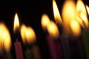 Candles burning in the dark. Close up image of candle flames. photo