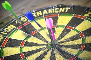 A dart board in black and yellow with colorful arrows. photo