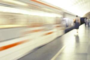 imagen borrosa de un tren en movimiento y siluetas humanas en el andén. foto