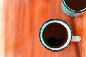 Cup of brewed black coffe on the wooden table photo