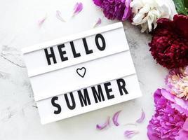 caja de luz con texto de hola verano y peonías. foto