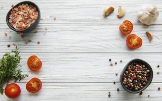 Tomate, albahaca y pimiento con ajo sobre fondo de madera blanca foto