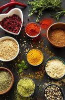Hierbas y especias coloridas y aromáticas sobre un fondo oscuro foto