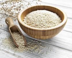 Sesame seeds in a bowl  on a rustic table photo