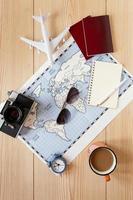 Arreglo de viaje con mapa y cámara sobre fondo de madera foto