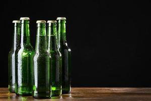 Green beer bottles on black background photo