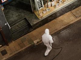 Spain, Mar 2020 - Man sanitizing a sidewalk photo