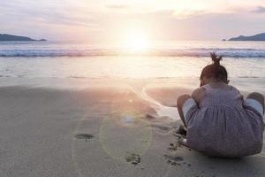 Girl playing in the sand at sunset photo