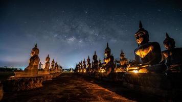 Milky way galaxy over many of buddha statues at Nakhon Si Thammarat, Thailand photo